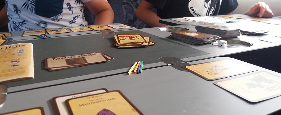 Munchkin-peli tanskalaisen EC-junan pöydällä, levelit merkittynä puutikuilla.